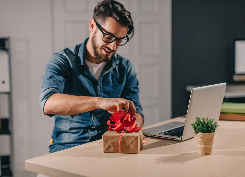 Man opening gift sitting at desk